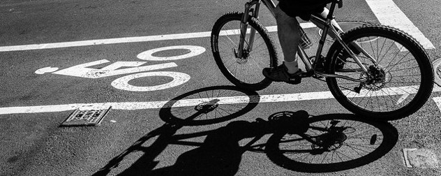 black and white image of a bike lane, with a bike rider and their shadow