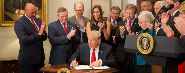 President Trump signs an executive order in the Roosevelt Room at the White House while observers applaud