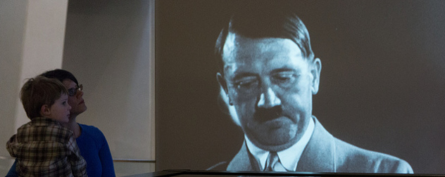 a woman and child looking at a video screen with an image of Hitler