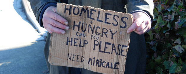 cardboard sign that reads 'Homeless & Hungry Can You Help Please Need Miracle'