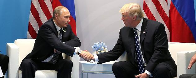 Vladimir Putin and Donald Trump, seated, shaking hands