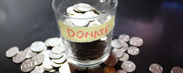 glass with tape labeled Donate, full of coins