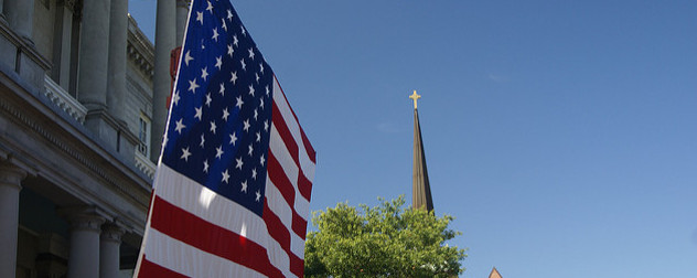 American flag in foreground, steeple in the back