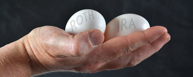 hand holding two eggs with the words 'Roth' and 'IRA' against a black background