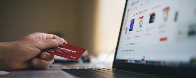 hand holding credit card in front of laptop displaying eBay shopping screen