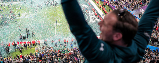 an Eagles fan celebrates in the foreground as confetti falls on the field after the 2018 Super Bowl