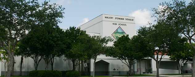 front facade of Marjory Stoneman Douglas High School, partly covered with trees