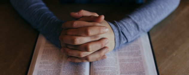hands folded, as in prayer, resting on an open book