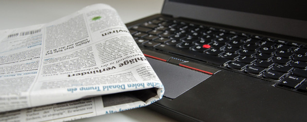folded newspaper resting against an open laptop