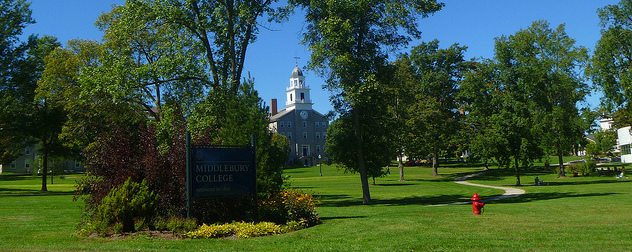 Middlebury College sign with building visible through tress in the background