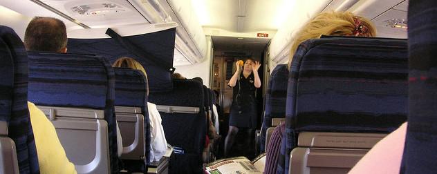 flight attendant demonstrating how to tighten a passenger oxygen mask