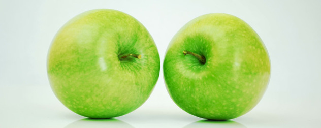 two green apples against a white background