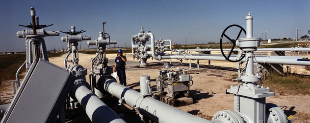 worker standing among wellhead and valves at Bryan Mound, an SPR storage site