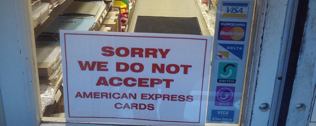 sign in a shop window that reads 'Sorry We Do Not Accept American Express Cards'