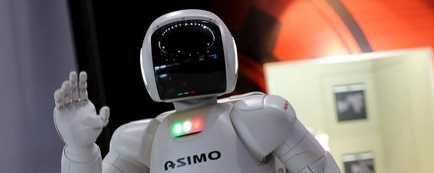 Asimo, a humanoid robot by Honda, waving at the camera