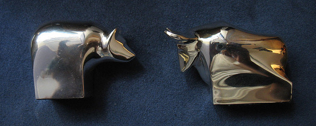 brass bear and bull paperweights against a navy blue velvet background