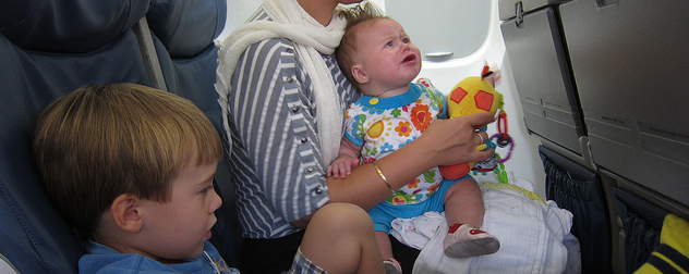 upset toddler in an adult's lap on an airline seat, with a slouching child in the adjacent seat