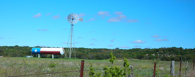 water tank painted to resemble the Texas flag in a field, next to a windpump