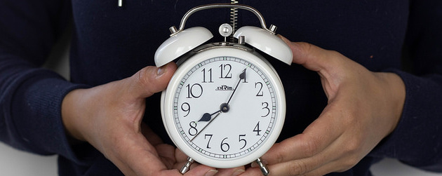person holding an old-fashioned analog alarm clock just below chest height