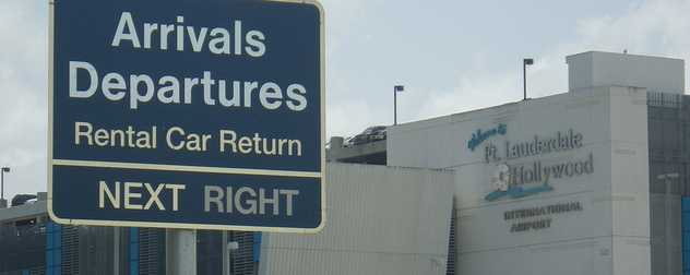 Arrivals-Departures sign in foreground with Ft. Lauderdale Hollywood International Airport facade in background