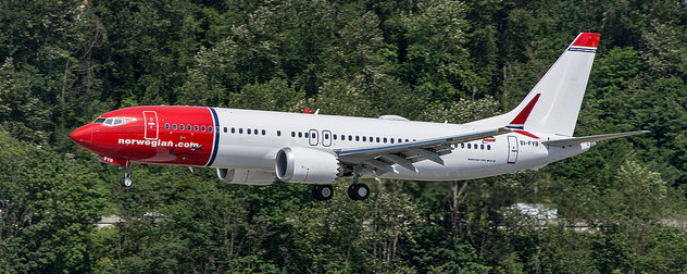 Norwegian Air Shuttle Boeing 737 MAX 8 in flight against trees
