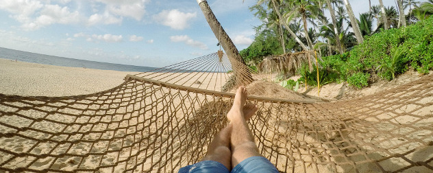 a person in jean shorts in a hammock on a tropical beach