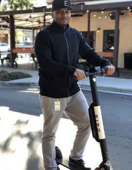Shomari Hearn posing with Bird electric scooter.