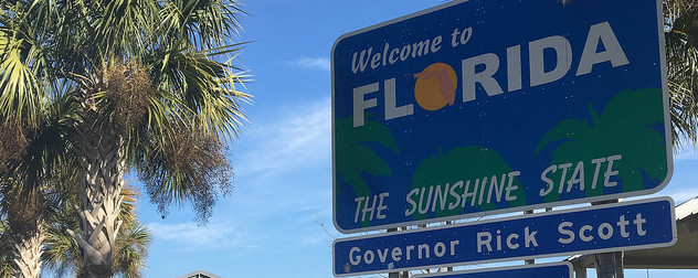 road sign reading 'Welcome to Florida, The Sunshine State' and 'Governor Rick Scott'