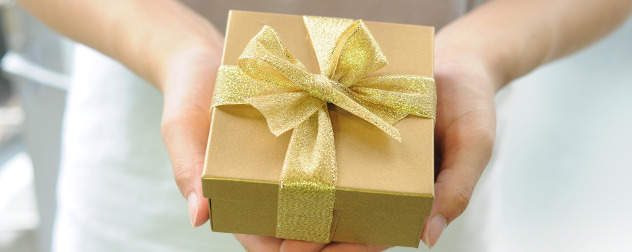 hands offering a gold gift box with a gold ribbon.