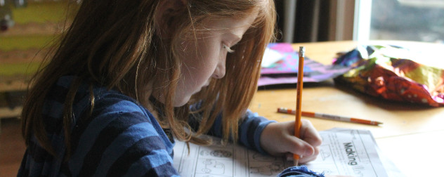 child with long hair works on homework worksheet at a table