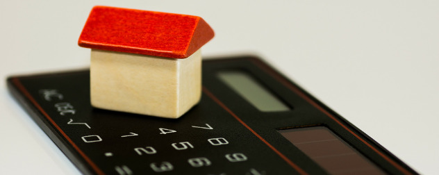 small wooden house resting on a simple calculator