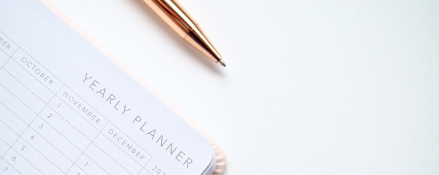 detail of a blank yearly planner and a ball-point pen.