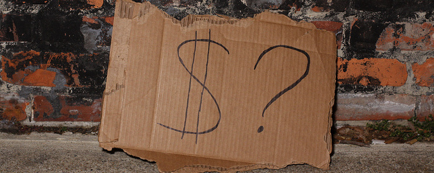 cardboard sign, possibly from homeless person, with the simple message '$?' propped against a brick wall.