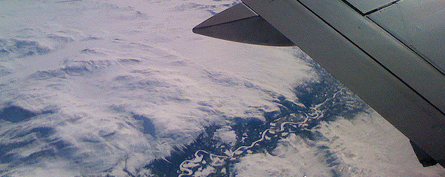 aerial view of a snowy landscape with a river, and part of a commercial airplane wing.