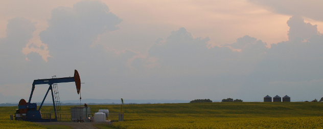 Alberta landscape with a pumpjack, grain silos and field against a sunset.