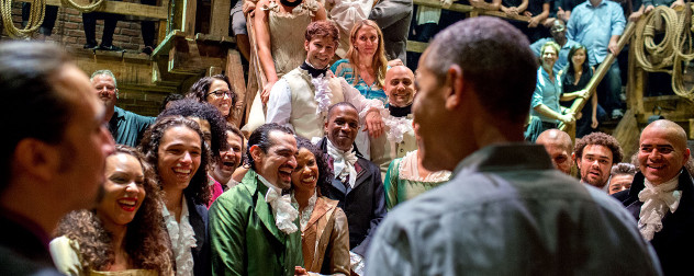 Barack Obama, shot from behind, interacting with the original cast and crew of the Broadway musical 'Hamilton' on the show's set.