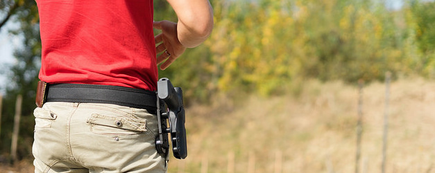 detail of a person with a red shirt and khakis wearing a handgun in a hip holster.