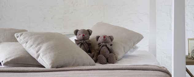 two small teddy bears on a bed.