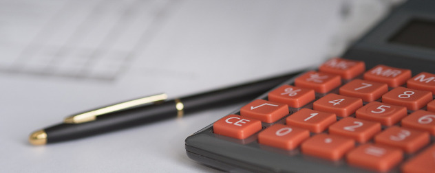 detail of a calculator, with a ballpoint pen and papers out of focus in the background.
