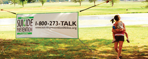 outdoor banner advertising the National Suicide Prevention Lifeline with a telephone number and a URL.
