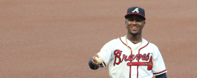 Ozzie Albies in uniform for the Atlanta Braves, holding a baseball.