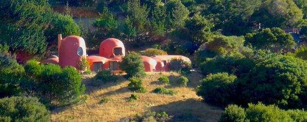 the Flintstone House in an all-orange paint job, seen from a distance.