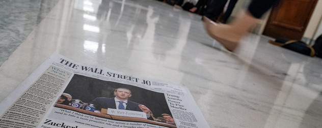print issue of The Wall Street Journal on a marble floor, a person walking by in the background.