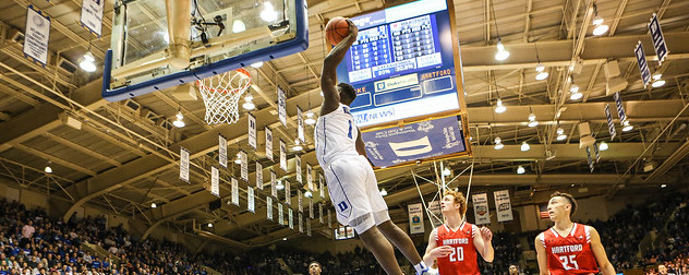 Zion Williamson, midair, about to make a basket as opposing players look on.