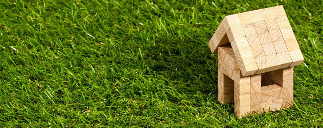 small wooden model house on grass.