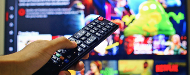 hand pointing a remote control at an out-of-focus TV screen with a streaming video service player menu displayed.