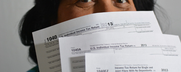person holding paper versions of IRS Form 1040, 1040A and 1040EZ in front of their face, mostly obscuring it.