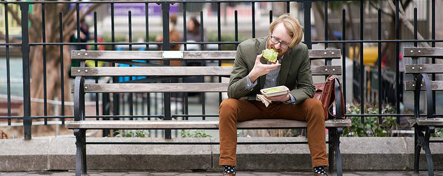 person with short hair and glasses sitting on a park bench eating avocado toast.