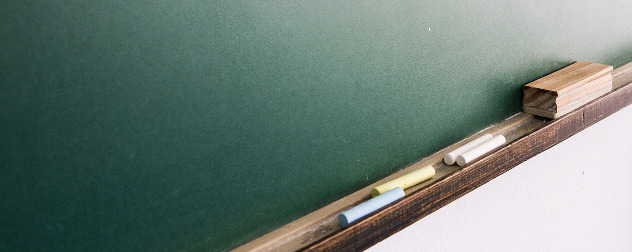 detail of blank blackboard with eraser and chalk.
