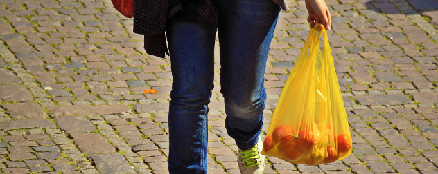 shopper carrying a plastic bag full of oranges